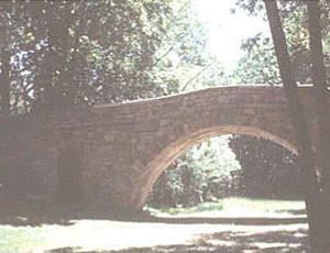 A stone bridge over a walking path in a wooded area
